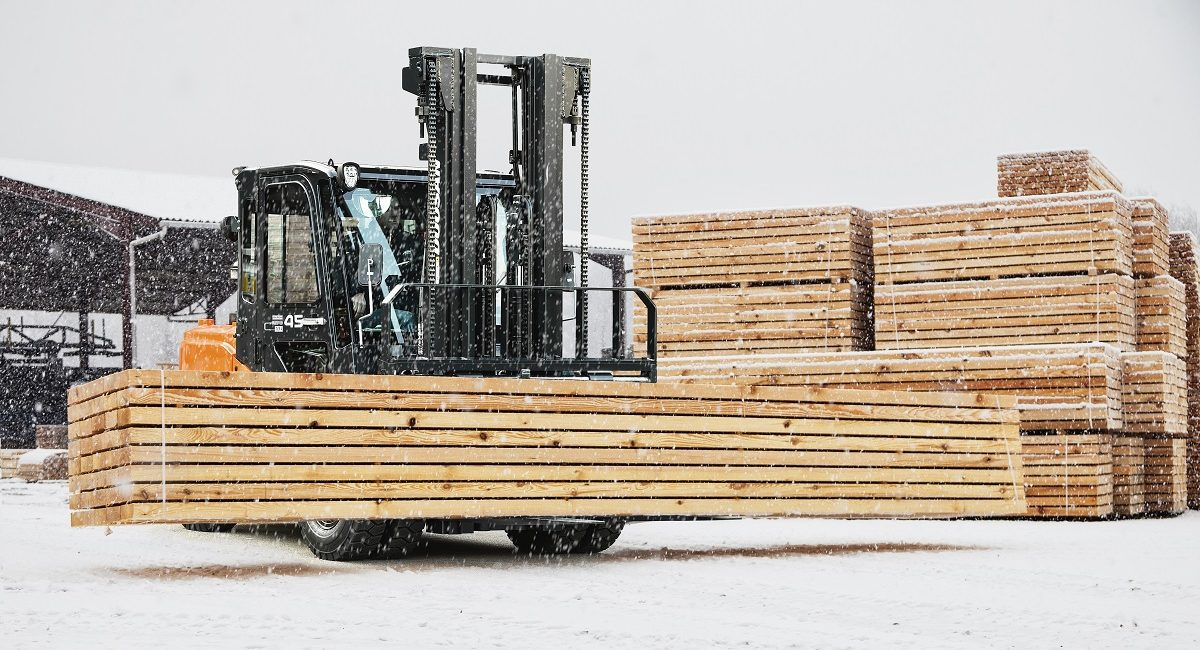 Truck moving stacks of wood planks in a lumberyard in winter